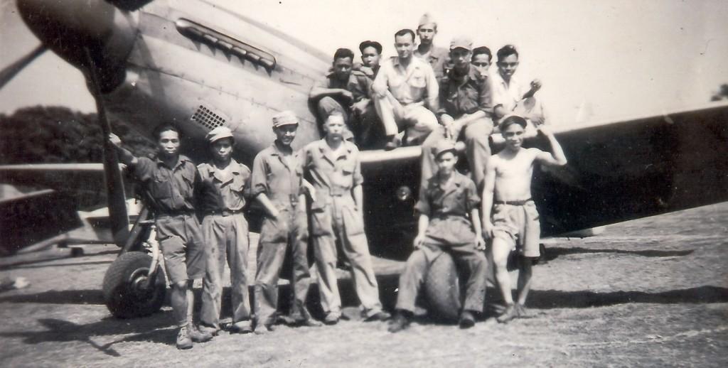 Boy staat enige met bloot bovenlijf de jongens staan voor een P-51 Mustang