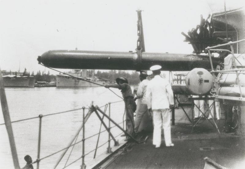 Torpedobootjager Hr.Ms. Piet Hein takelt een torpedo aan boord.